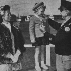 5-year-old Sharon Vance is presented with her father's Medal of Honor in 1946. US Army Photograph.