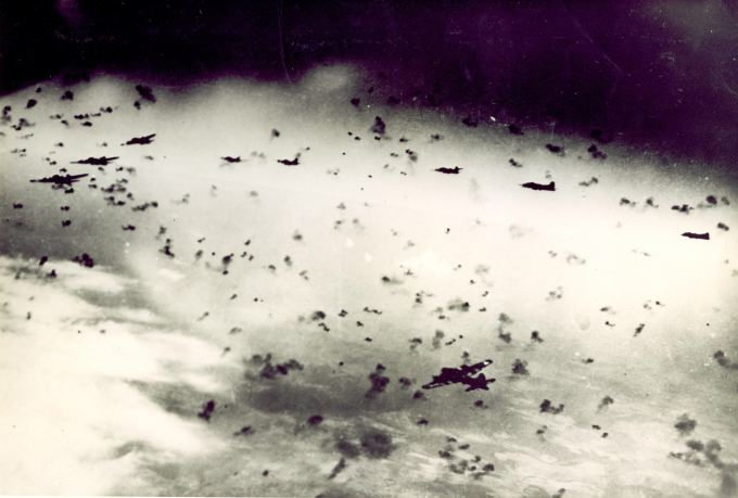 "B-17s from the 303rd flying through intense anti-aircraft fire.  Photo by Joseph Sassone with caption: ""Flak so thick you could almost taxi around it."""