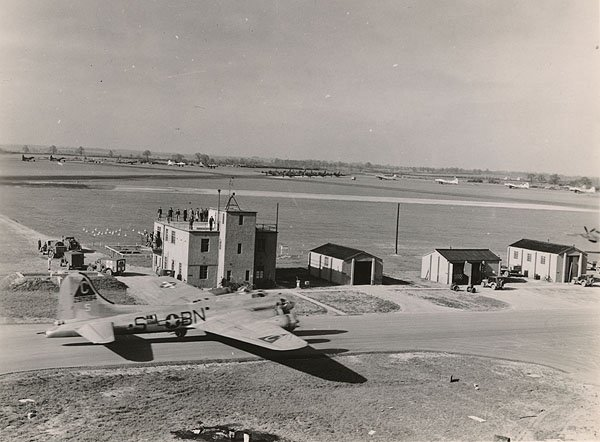 "The RAF Molesworth control tower in April 1944.  On the taxiway is a B-17G, tail number 42-97284 ""Ain't Misbehavin"" - she would fly a total of 48 combat missions during the war.  The ""Triangle-C"" designator on the verticle stabilizer was the RAF Molesworth designator.  Photograph by Mr. Milton ""Chic"" Cantor, the photographer of the 303rd BG(H), with thanks to the 303rd ""Hell's Angels"" historical society."