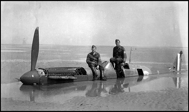 MK1 Spitfire P9374 on the beaches of Dunkirk in Spring 1940 with two German servicemen on her fuselage. © BNPS.
